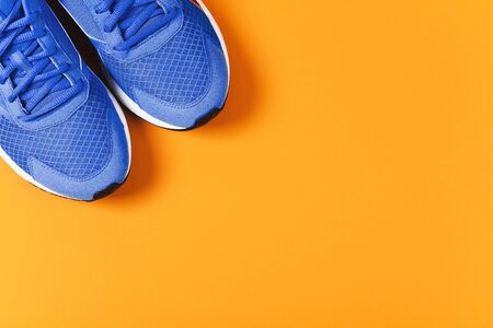Blue sneakers on orange background. Concept of healthy lifestile