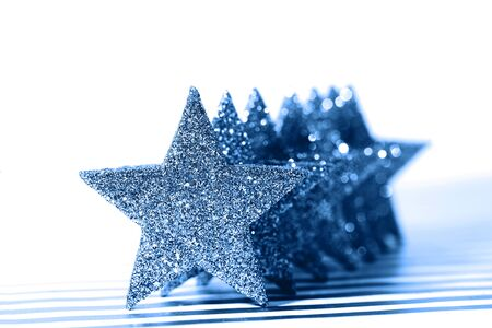 Textured glittering blue stars on white background. Demonstration of color of the year. Фото со стока