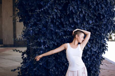 Authentic girl dances over blue plant in the city. Girl is short-haired. Фото со стока