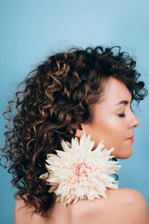 Sensuality young curly woman with closed eyes is holding in her mouth white chrysanthemum flower on blue background. Wellness concept.