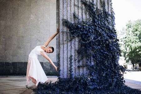 Authentic girl dances over blue plant in the city. Girl is short-haired.