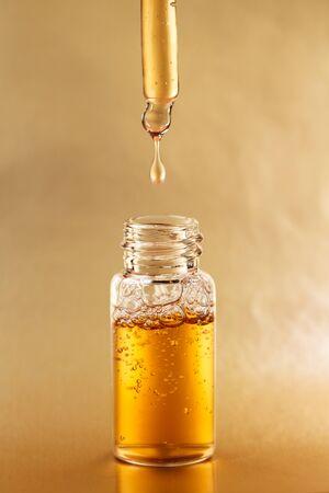Flasche kosmetisches Öl mit Pipette auf goldenem Hintergrund. Vorderansicht. Standard-Bild