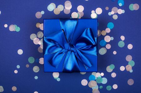 Blue present box with bow in monochrome trendy flat lay composition with confetti Фото со стока