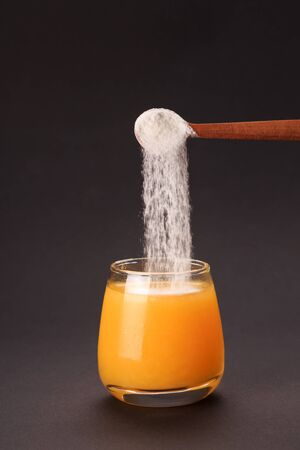 Orange juice with spoon of protein or collagen. Food supplement concept Фото со стока