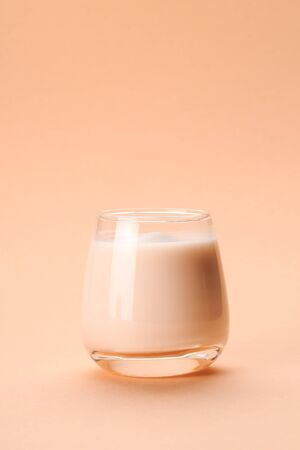 Coconut or almond milk with collagen on pastel coral background Фото со стока