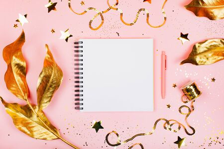 Note book on pink background with golden decorations. Festive concept in flat lay style