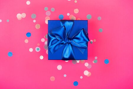 Blue present box with bow in monochrome trendy flat lay composition