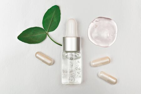 Bottle with hyaluronic acid on silver background. Concept of modern beauty. Flat lay style. Фото со стока
