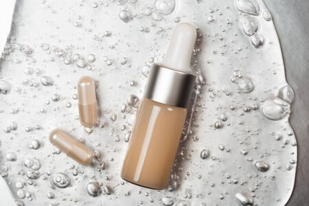 Bottle of hyaluronic acid and capsules of collagen on background with oxygen bubbles on silver background.