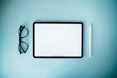 Digital tablet on blue background. Flat lay style. Clean white screen for your text