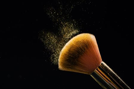Make-up brush on black. Front view. Falling sparkles. Ispired by color of the year 2020