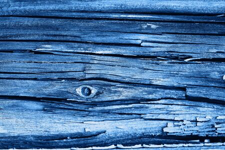Old wood texture with deep cracks and peeling blue paint Фото со стока