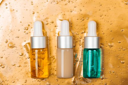 Three bottles of hyaluronic acid and collagen on background with oxygen bubbles on golden luxury background.