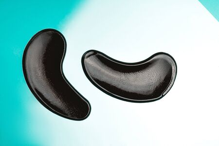 Black eye patches with collagen on bright background