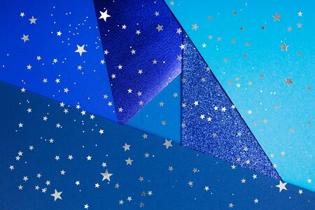 Divided in several parts blue paper background with metallic elemments and silver stars. Inspired by color of the year 2020