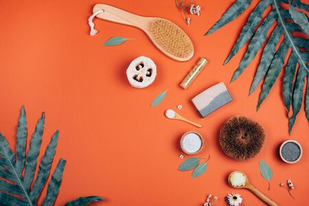 Collagen powder or white clay on orange background with palm leaf. Flat lay style.