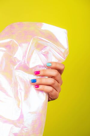 Female hand with trendy ideal neon manicure with holographic surface in it. Beauty concept.