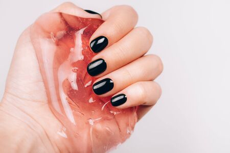 Hands with black manicure holding transparent slime Фото со стока