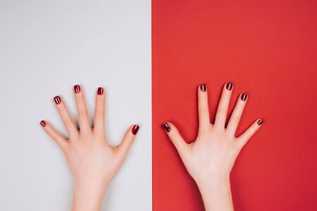 Red beautiful manicure on red and grey stylish background with copyspace. Flat lay style.