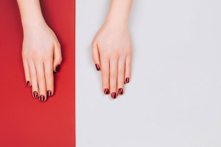 Red beautiful manicure on red and grey stylish background with copyspace. Flat lay style. Archivio Fotografico