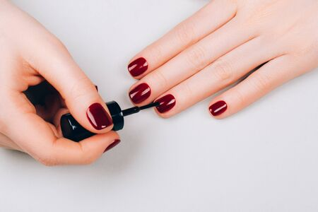Woman making red manicure by herself on grey background. Archivio Fotografico