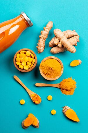 Turmeric in different states: fresh in bottle, pills, powder and cut plant on wooden tray, dry root in wooden bowl. 版權商用圖片