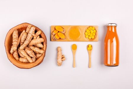 Turmeric in different conditions: fresh in bottle, pills, powder and cut plant on wooden tray, dry root in wooden bowl. Flat lay style.