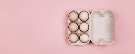 Banner made with Organic eggs in carton tray on pastel pink backgroud. Zero Waste concept. Flat lay style. Standard-Bild