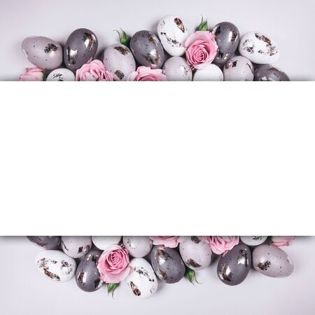 Group of Easter eggs and flowers with Plase for text on grey background.