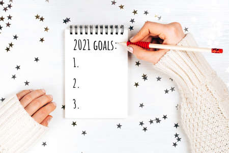 Holiday decorations and notebook with new year resolutions list on white rustic table, flat lay style. Planning concept for 2021 Foto de archivo