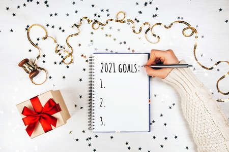 Holiday decorations and notebook with new year resolutions liston white rustic table, flat lay style. Planning concept for 2021