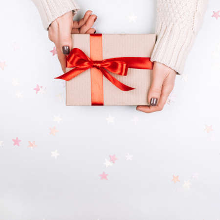 Womans hands holding cardboard present box with red bow on white background with multicolored star confetti. Square shape for social media Stock Photo