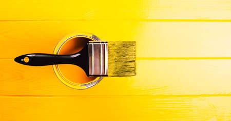 Banner made with opened can of yellow paint with brush on it. Yellow freshly painted wooden background.