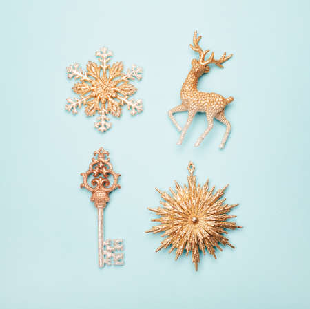 Accurate rows of four golden beautiful of Christmas ornaments on pastel blue background. Square shape for social media