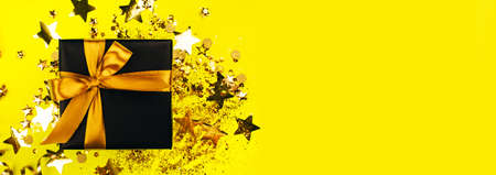 banner made with gift box with golden bow on bright yellow background with illuminatng confetti glitter. Holiday concept.