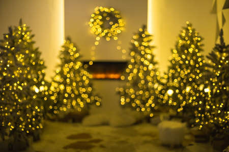 Defocused background of illuminated Christmas trees placed near fireplace with traditional wreath in evening in cozy room at home 版權商用圖片