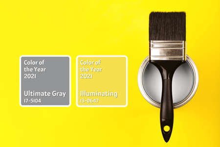 Demonstrating colors of year 2021 - Gray and Yellow. Brush with wooden handle on open can with frames. Renovation concept.
