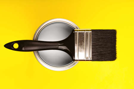 Demonstrating colors of year 2021 - Gray and Yellow. Brush with wooden handle on open can. Renovation concept.