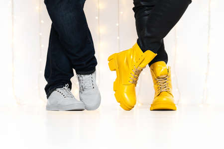 Demonstrating trendy colors of year 2021 - Gray and Yellow. Closeup unrecognizable people in stylish boots. 免版税图像