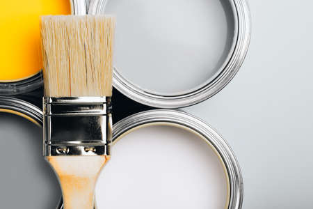 Demonstrating trendy colors of year 2021 - Gray and Yellow. Brush with wooden handle on open cans. Renovation concept. Macro. 免版税图像