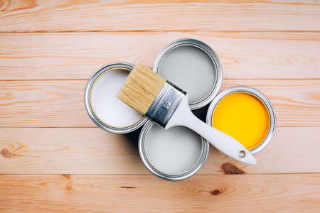 Demonstrating colors of year 2021 - Gray and Yellow. Four open cans of paint with brush on them on wooden natural background. Top view.