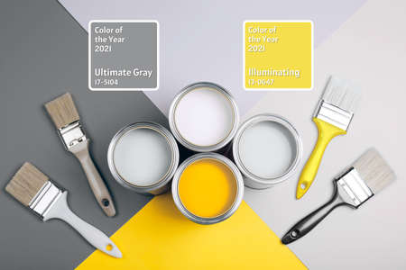 Demonstrating colors of year 2021 - Gray and Yellow. Four open cans of paint with brushes on bright background.
