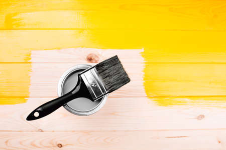 Paintbrush is applying on yellow half freshly painted wooden background. Repairing concept.