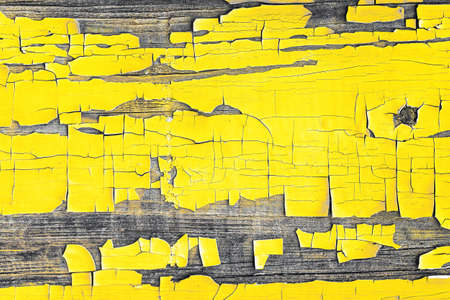 Demonstrating trendy colors 2021 - Gray and Yellow. Background made of yellow, peeling paint on an old wooden wall 免版税图像