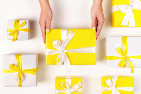 Demonstrating trendy colors of year 2021 - Gray and Yellow. Colorful gifts with ribbons