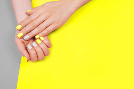 Stylish trendy female manicure. Beautiful young womans hands on gray and yellow background.