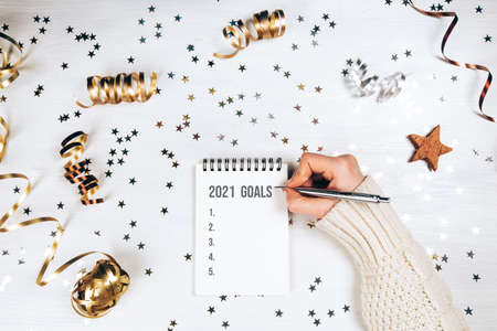 Holiday decorations and notebook with 2021 goals on white rustic table, flat lay style. Christmas planning concept. 免版税图像