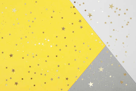 Paper background with metallic shiny stars and glitter in two trendy colors - yellow and gray. Demonstrating colors of the year. Festive backdrop for your design. 免版税图像
