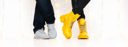 Banner made with unrecognizable people in bright yellow boots and sneakers standing against white wall with fairy lights