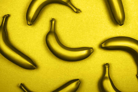 Yellow metallic bananas on monochrome background. Flat lay style. Trendy photo ispired by color of the year 2021
